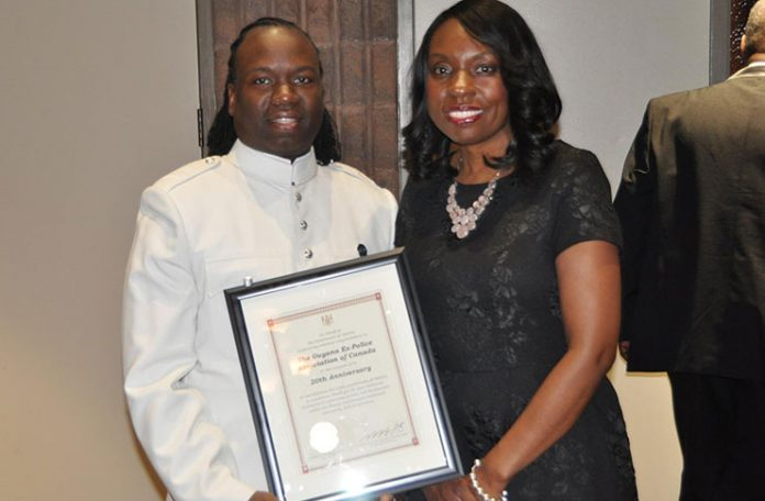 Ontario's Minister of Education, Mitzie Hunter, presents commemoration plaque to  GEPAC's president, John O'Dell.
